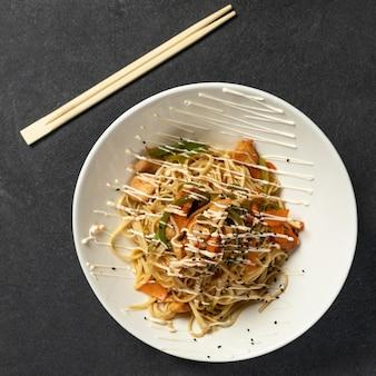 Prato de macarrão e legumes chow mein com pauzinhos de madeira na mesa preta