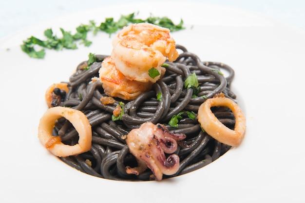 Prato de macarrão italiano de espaguete preto com queijo ralado servido na mesa