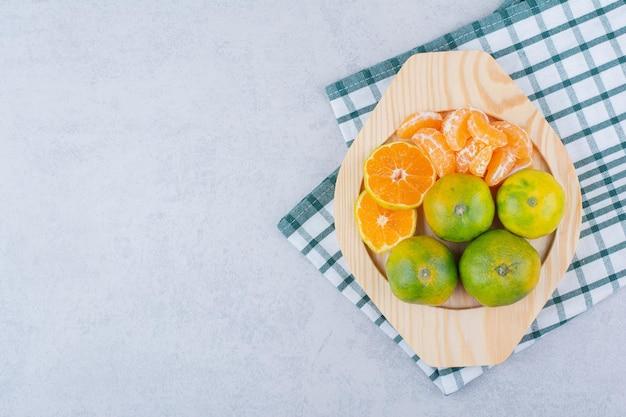 Prato de madeira cheio de tangerinas ácidas em fundo branco. foto de alta qualidade