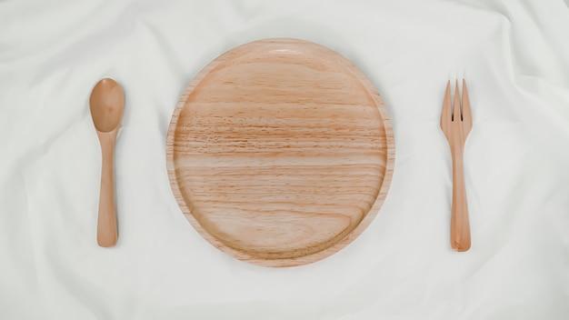 Prato de madeira, colher de madeira e garfo de madeira em pano branco. vista superior da configuração da mesa em fundo branco