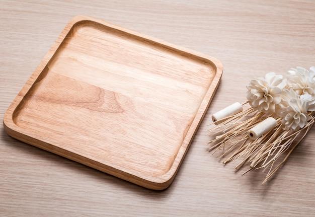 Prato de madeira com a flor secada no de madeira.