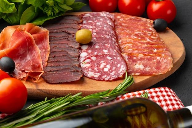 Prato de madeira com cortes de carne de perto