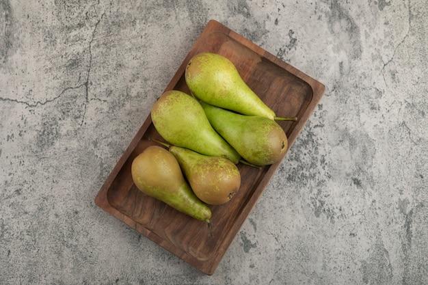 Prato de madeira com deliciosas peras maduras em fundo de mármore