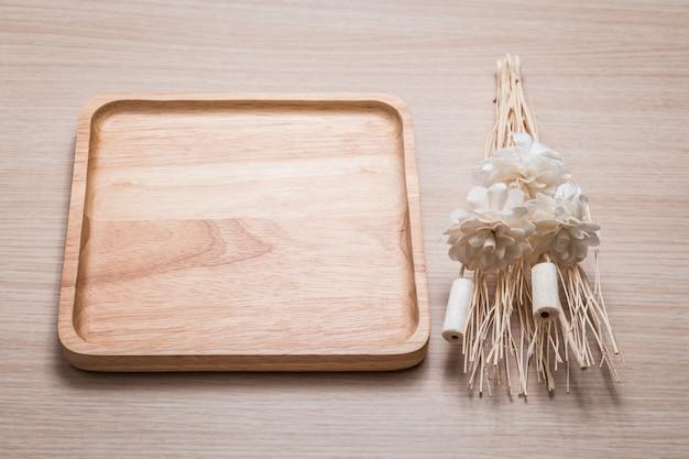 Prato de madeira com flores secas no fundo de madeira.