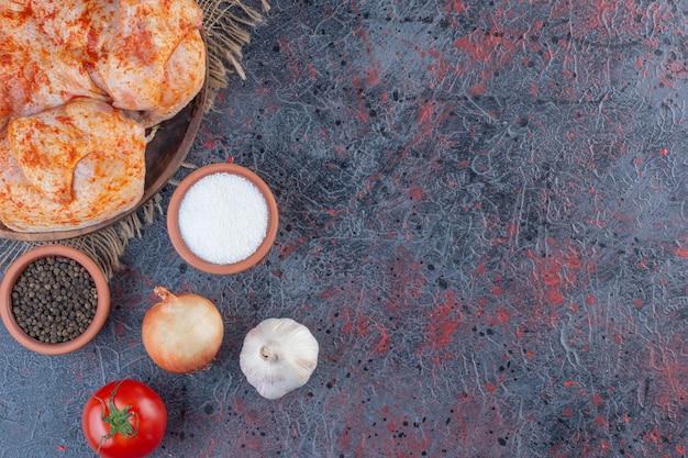 Prato de madeira com frango inteiro marinado em superfície de mármore