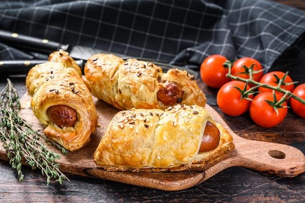 Prato de madeira com rolinhos de salsicha na massa