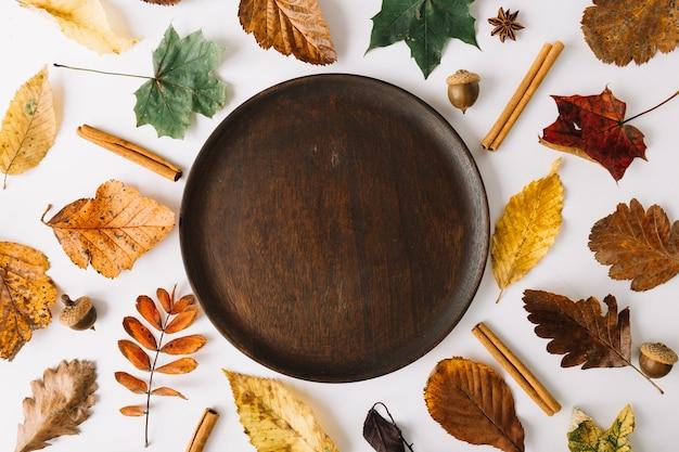 Prato de madeira entre folhas outonais