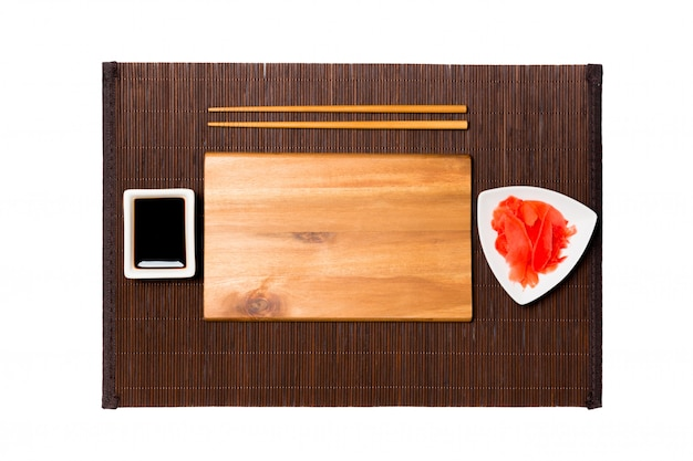 Prato de madeira marrom retangular vazio com pauzinhos para molho de sushi, gengibre e soja no fundo de esteira de bambu escuro. vista superior com espaço de cópia para você projetar
