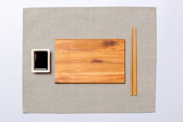 Prato de madeira marrom retangular vazio com pauzinhos para sushi e molho de soja, guardanapo cinza