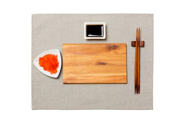 Prato de madeira marrom retangular vazio com pauzinhos para sushi, gengibre e molho de soja, guardanapo cinza. vista superior com copyspace