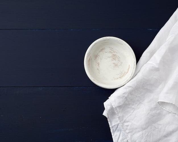 Prato de madeira redondo e toalha de linho branco na superfície de madeira azul
