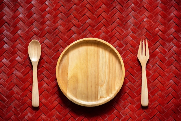 Prato de madeira vazio com colher e forquilha na textura do bambu tecido.