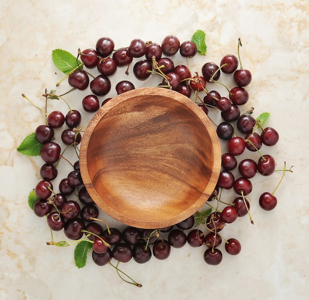 Prato de madeira vazio e espalhados em torno dele cerejas