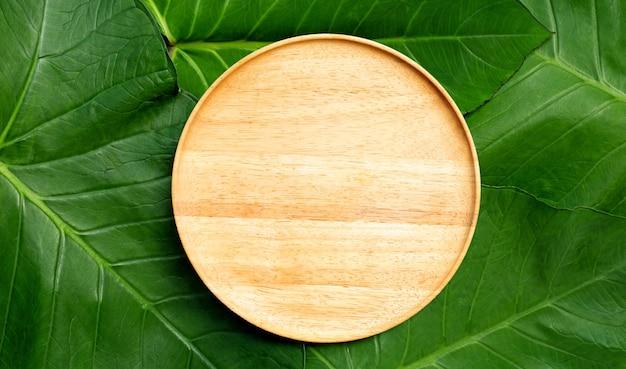 Prato de madeira vazio em folhas de taro. vista do topo