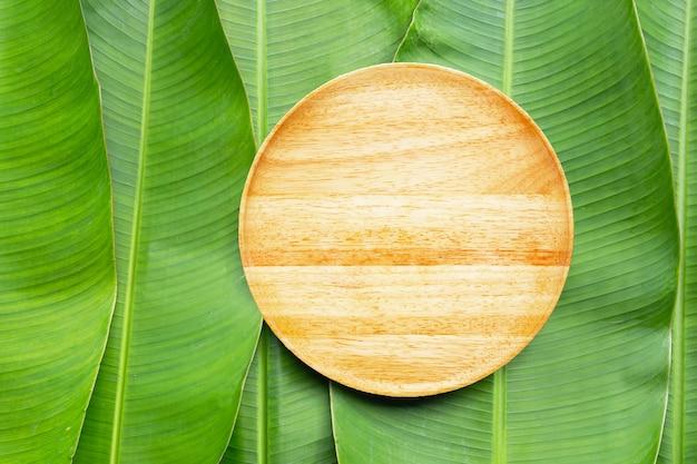 Prato de madeira vazio em fundo de folhas de bananeira. vista do topo