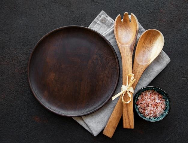 Prato de madeira vazio em uma mesa preta