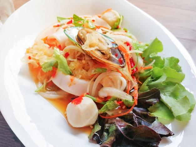 Prato de marisco de mistura de salada picante com camarão de mexilhão de lula e vegetais frescos servidos