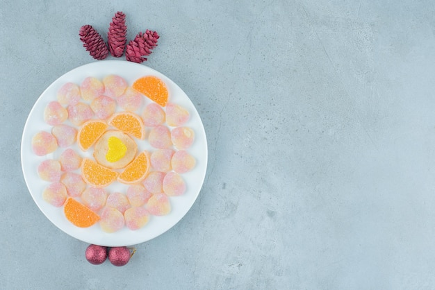 Prato de marmeladas variadas, com pinhas e bugigangas em mármore.