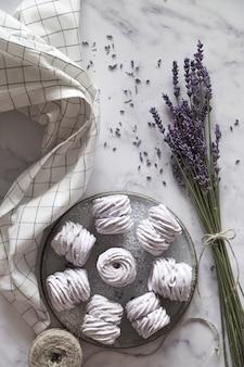 Prato de marshmallows caseiros (zéfiro, merengue) feitos com lavanda na pedra branca marmor