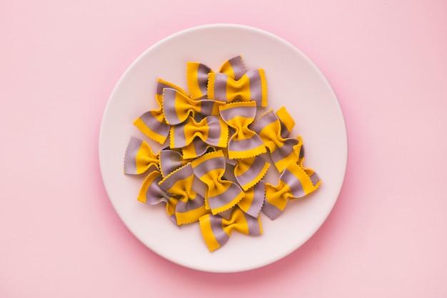 Prato de massa crua em forma de borboleta, amarelo e roxo. conceito de comida saudável