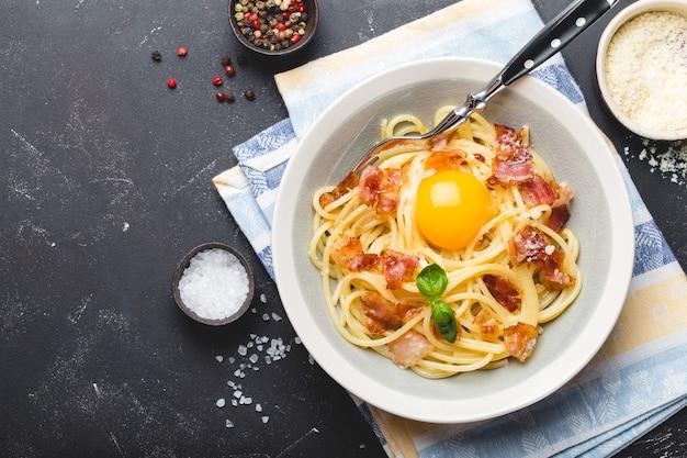 Prato de massa italiana tradicional, espaguete carbonara com gema, queijo parmesão, bacon em prato sobre fundo preto de pedra rústica