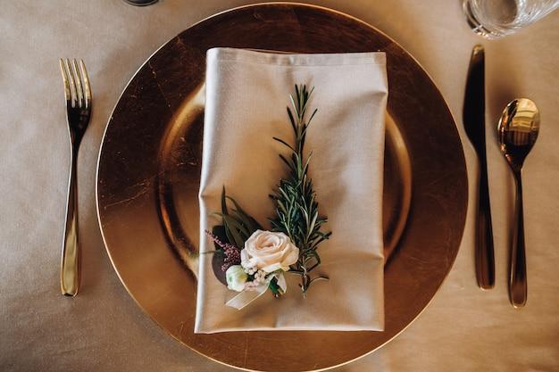 Prato de mesa servindo com folha de pinheiro e rosa em guardanapo
