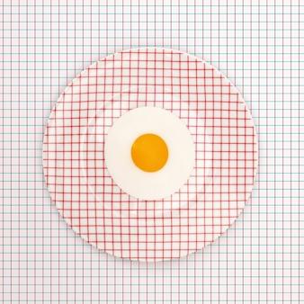 Prato de ovo frito em uma mesa com um padrão geométrico