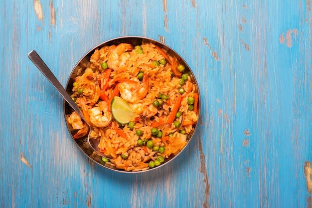 Prato de paella espanhola tradicional com frutos do mar, ervilhas, arroz e frango