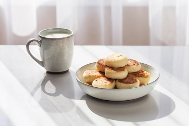 Prato de panquecas e copo de leite na mesa branca. café da manhã ou almoço saudável. luz do sol e sombra.
