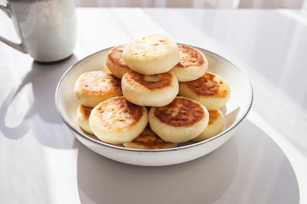 Prato de panquecas na mesa branca. café da manhã ou almoço saudável. luz do sol e sombra.