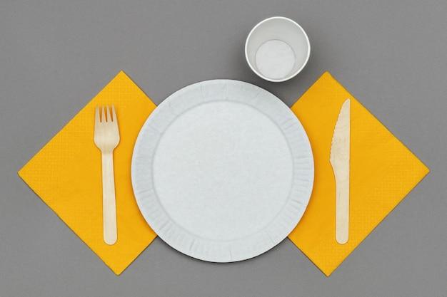 Prato de papel e copo, garfo de madeira e faca em guardanapo laranja em fundo cinza, vista superior. conjunto de talheres descartáveis ecológicos de material natural.