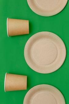 Prato de papel, vidro sobre um fundo verde. pratos compostáveis ecológicos, materiais descartáveis e recicláveis. plástico zero, salvando o planeta, pare de plástico. o conceito de reciclagem de resíduos