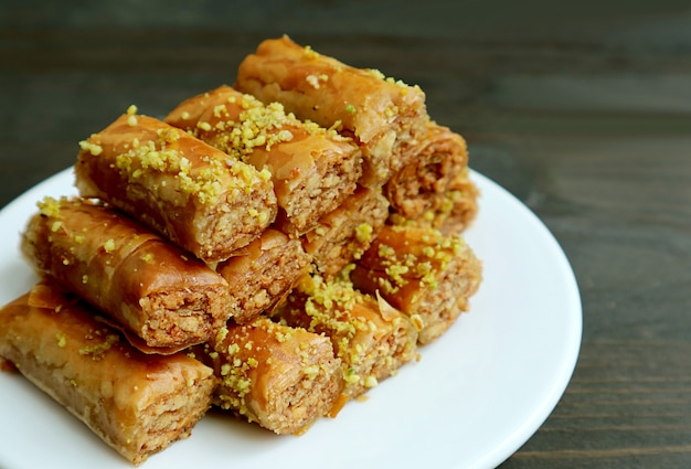 Prato de pastelaria crocante e doce de baklava com nozes de pistache na superfície de madeira preta