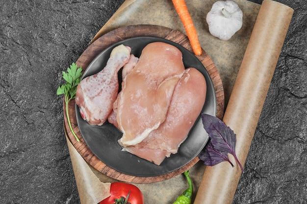 Prato de pedaços de frango cru com tomate e cenoura na superfície escura