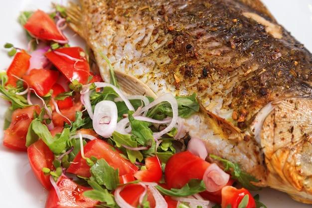 Prato de peixe. carpa crucian fritada com salada verde