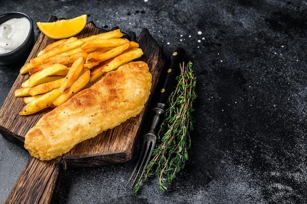 Prato de peixe com batata frita e batata frita em tábua de madeira