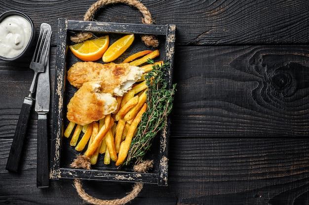 Prato de peixe com batata frita empanado com batata frita e molho tártaro em bandeja de madeira. fundo de madeira preto. vista do topo. copie o espaço.