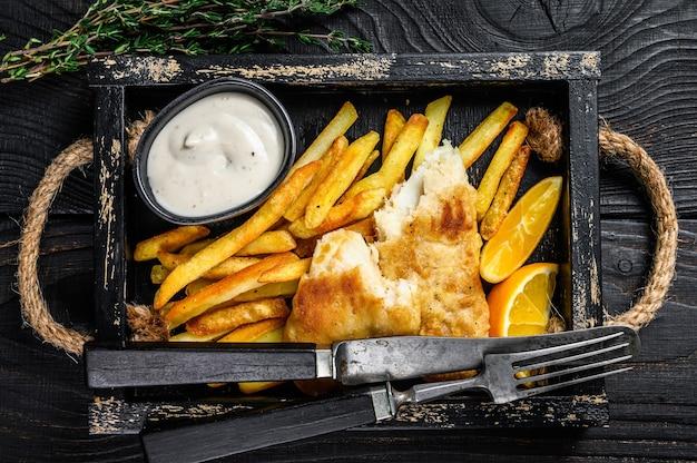 Prato de peixe com batata frita empanado com batata frita e molho tártaro em bandeja de madeira. fundo de madeira preto. vista do topo.