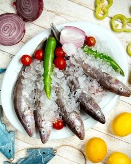 Prato de peixe cru coberto com pimenta, tomate cereja e cebola vermelha