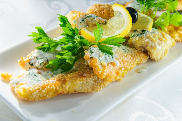 Prato de peixe - filé de peixe frito com legumes no fundo branco