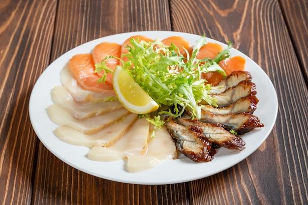 Prato de peixe misto na mesa de madeira