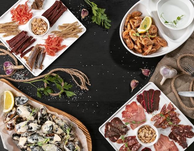 Prato de peixe seco com frios, camarões e mexilhões na mesa de madeira preta