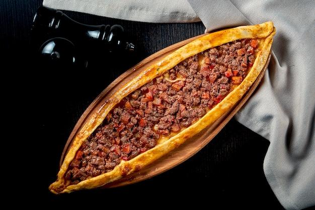 Prato de pide turco com fatias de carne, tomate na mesa preta