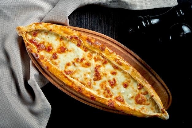 Prato de pide turco com tomate e queijo salgado na mesa preta