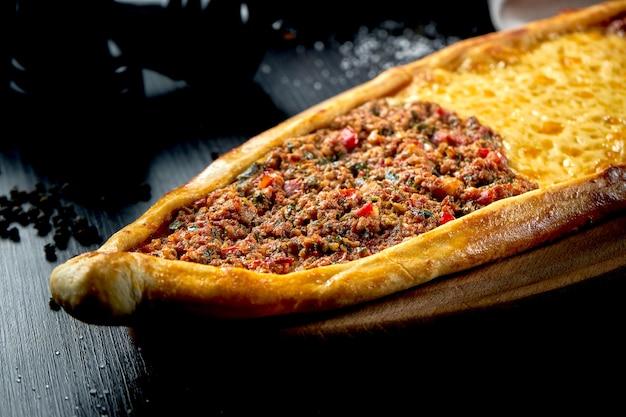 Prato de pide turco com três recheios diferentes: cordeiro, boi e queijo cheddar em mesa preta. close up, foco seletivo