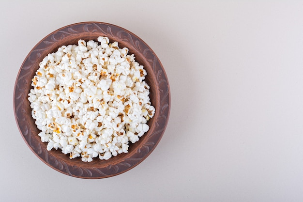 Prato de pipoca salgada para noite de cinema em fundo branco. foto de alta qualidade
