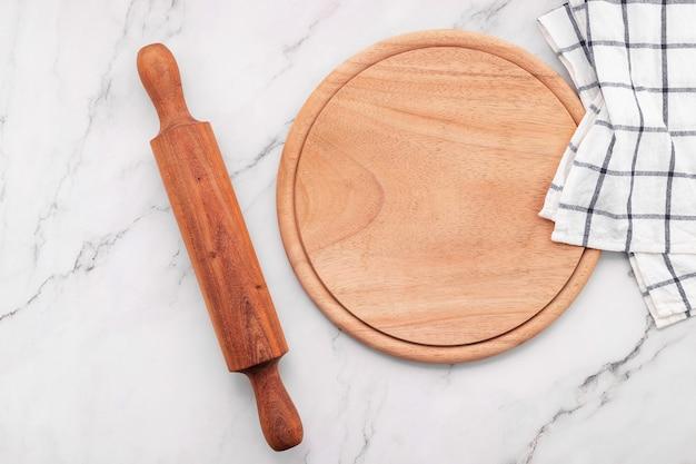 Prato de pizza de madeira vazio com guardanapo e rolo de massa criado na mesa da cozinha de pedra de mármore. placa de pizza e toalha de mesa em fundo de mármore branco.