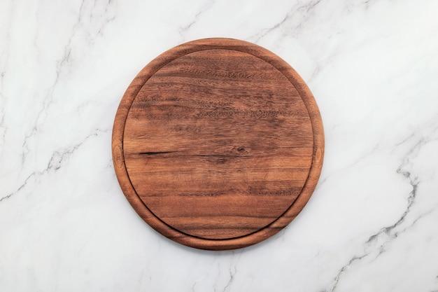 Prato de pizza de madeira vazio montado na mesa da cozinha de pedra de mármore. placa de pizza no plano de fundo de mármore branco leigos e copie o espaço.