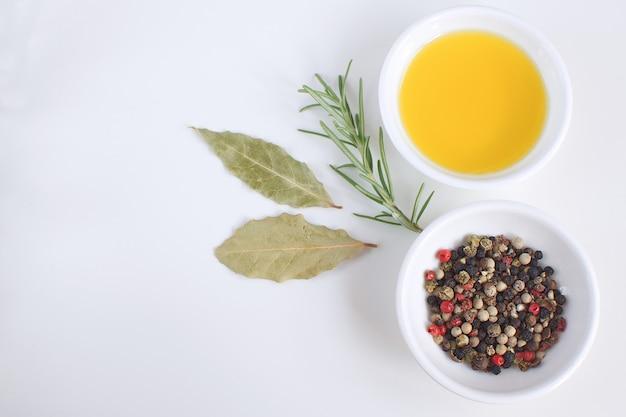 Prato de porcelana com azeite de oliva ramo de alecrim mistura de pimenta folha de louro