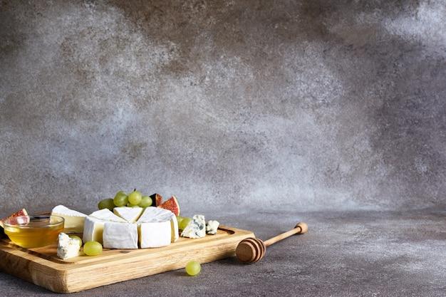 Prato de queijo camembert e queijo azul com uvas, figos, mel em uma placa de madeira. prato de queijos